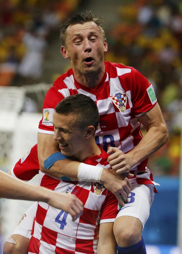 Croatia's Ivan Perisic celebrates after scoring a goal with teammate Ivica Olic (top) during their 2014 World Cup Group A soccer match against Cameroon at the Amazonia arena in Manaus June 18, 2014. REUTERS/Yves Herman (BRAZIL - Tags: SOCCER SPORT WORLD CUP)