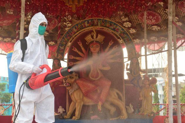 A healthcare worker is seen spraying a disinfectant inside a Durga Puja pandal in Kolkata in a file photo.