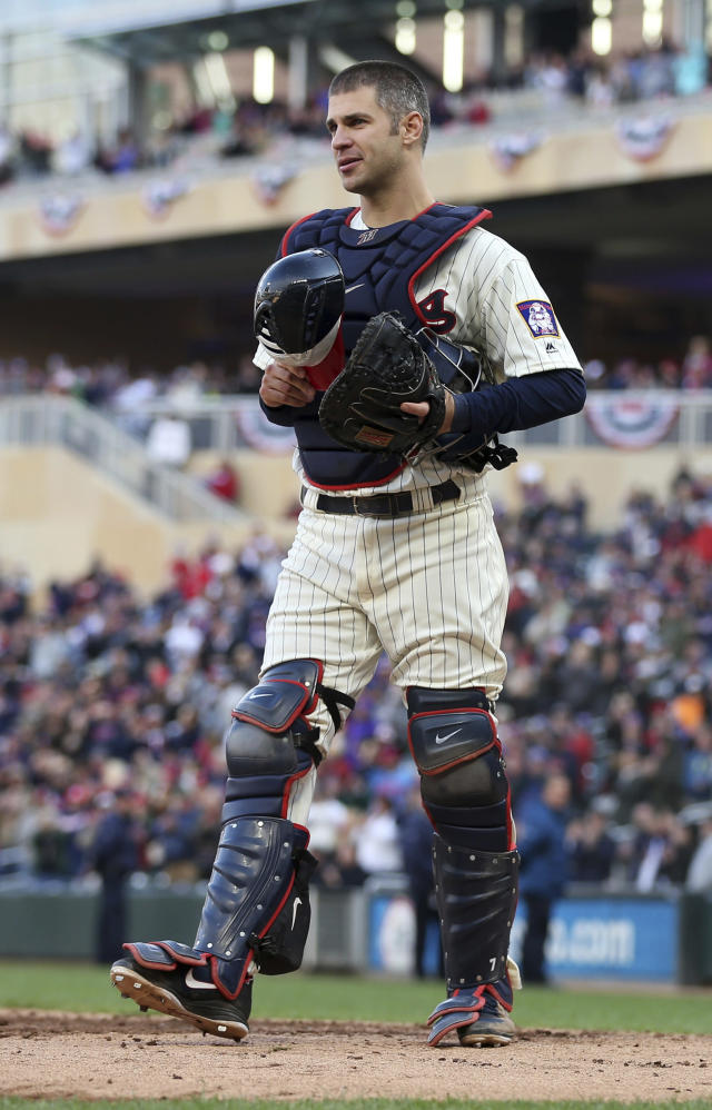 Minnesota Twins' Joe Mauer, the subject of retirement talk, acknowledges a standing ovation as he donned catcher's gear and caught for one pitch against a Chicago White Sox batter in the ninth inning of a baseball game Sunday, Sept. 30, 2018, in Minneapolis. Mauer began his career as a catcher before switching to first base. The Twins won 5-4. (AP Photo/Jim Mone)