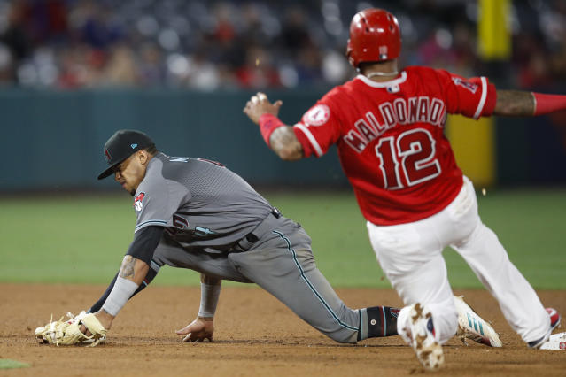 Arizona Diamondbacks' Ketel Marte, left, catches the throw to force out Los Angeles Angels' Martin Maldonado during the eighth inning of a baseball game Tuesday, June 19, 2018, in Anaheim, Calif. Maldonado was originally called safe, but, after review, he was ruled out. (AP Photo/Jae C. Hong)