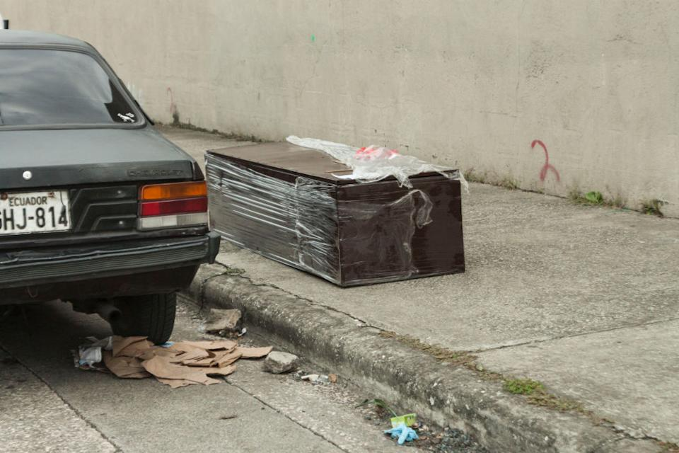 Pictured is a coffin on a footpath next to a car in Guayaquil, Equador.