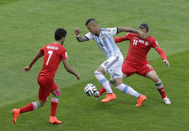 Argentina's Marcos Rojo takes the ball past Iran's Masoud Shojaei, left, and Iran's Andranik Teymourian during the group F World Cup soccer match between Argentina and Iran at the Mineirao Stadium in Belo Horizonte, Brazil, Saturday, June 21, 2014. (AP Photo/Sergei Grits)
