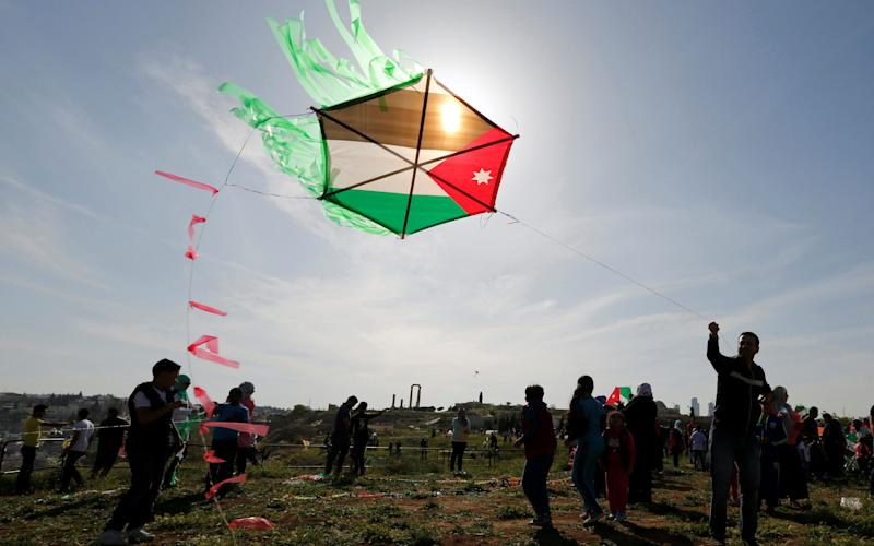People fly kites decorated with the Jordanian national flag during an event celebrating spring at the Citadel in Amman, Jordan - Credit: MUHAMMAD HAMED