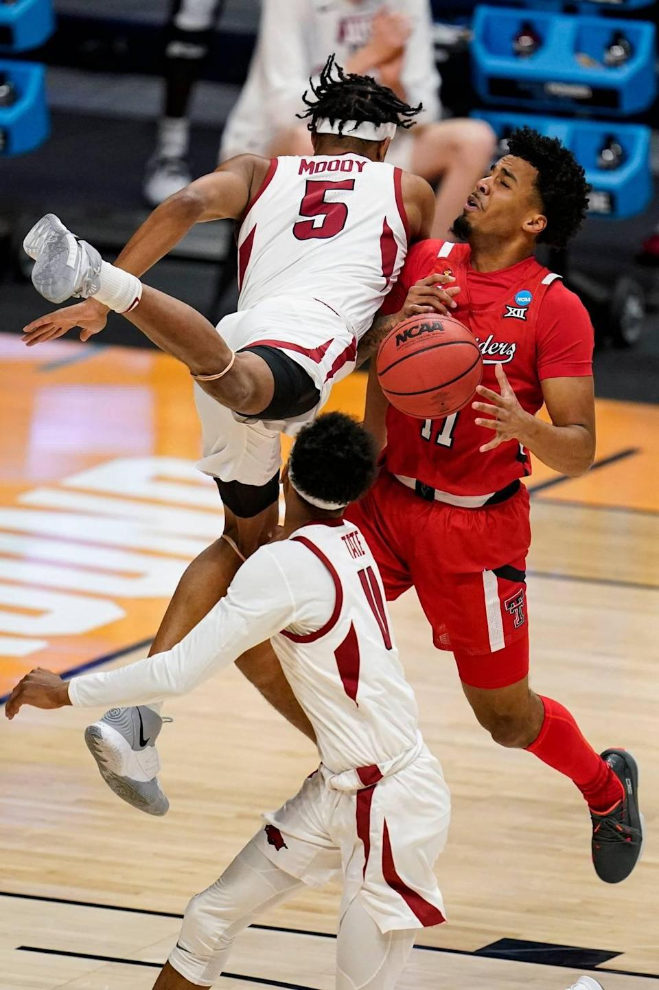 Arkansas guard Moses Moody (5) and Texas Tech guard Micah Peavy (5) collide in the first half of a second-round game in the NCAA men's college basketball tournament at Hinkle Fieldhouse in Indianapolis, Sunday, March 21, 2021.
