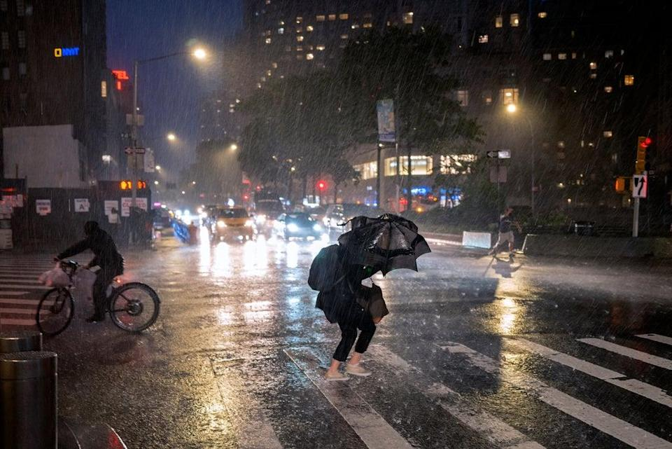 Pedestrians take cover near Columbus Circle in New York Wednesday, Sept. 1, 2021, as the remnants of Hurricane Ida remained powerful while moving along the Eastern seaboard (AP)