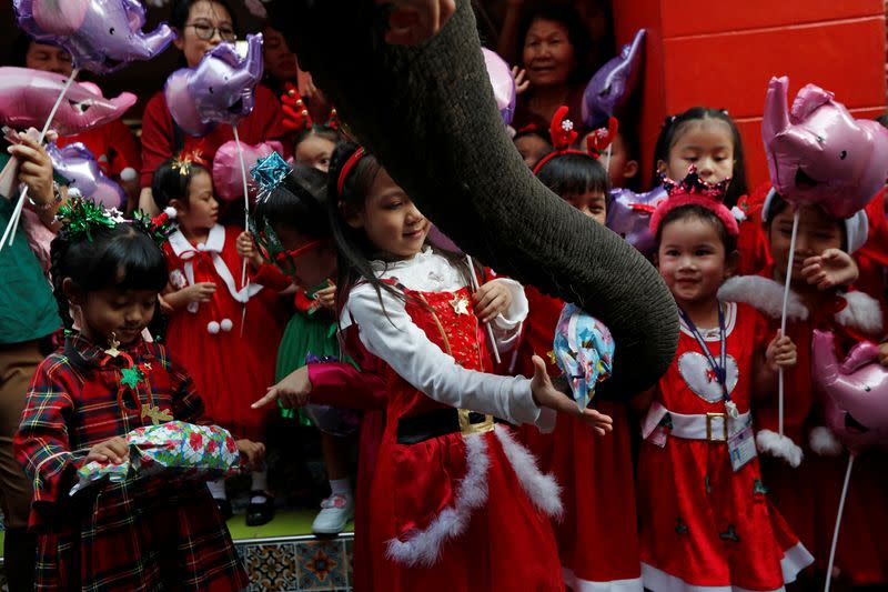 An elephant distributes Christmas presents to students at a school in Ayutthaya
