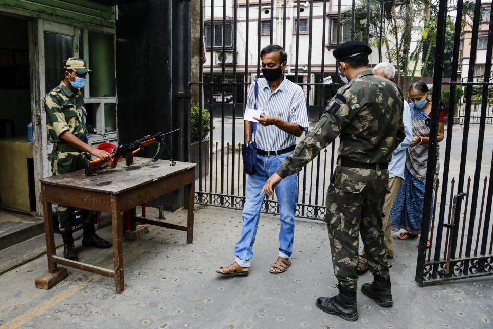 Paramilitary soldiers keep vigil as voters enter a polling station during the fourth phase of West Bengal state elections in Kolkata, India, Saturday, April 10, 2021. (AP Photo/Bikas Das)