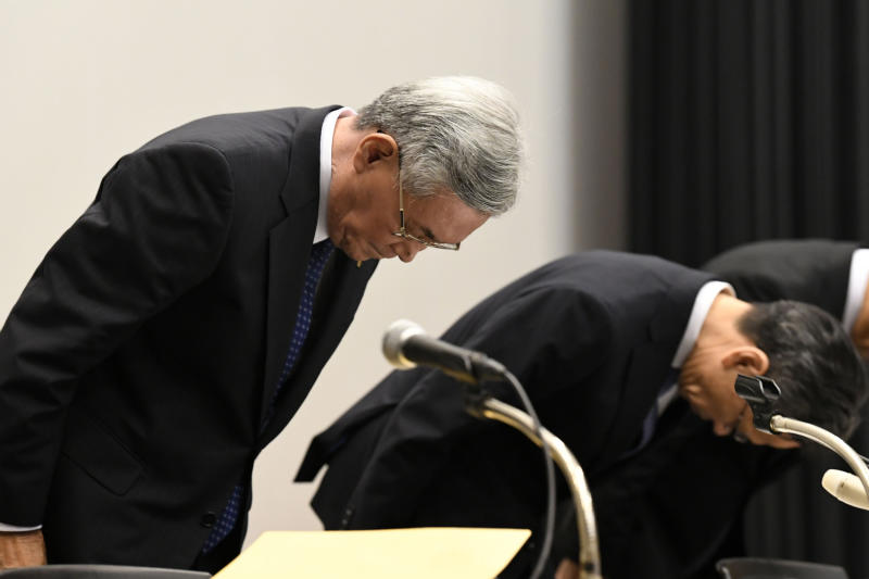 Kansai Electric Power Co. Chairman Makoto Yagi, left, bows in apology at the beginning of a press conference in Osaka, western Japan Wednesday, Oct. 9, 2019.  Yagi has resigned over a scandal involving 20 of its executives who received cash and lavish gifts totaling $3 million from a former official in a western Japan town where it operates a nuclear power plant. (Junko Ozaki/Kyodo News via AP)