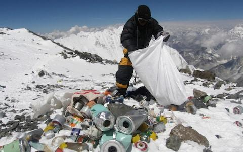 A Nepalese sherpa collects rubbish, left by climbers, during an Everest clean-up expedition - Credit: AFP
