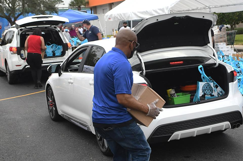 Volunteers load cars with turkeys and other food assistance for laid off Walt Disney World cast members and others at a food distribution event on December 12, 2020 in Orlando, Florida. Tom and Sarah Bricker, a couple who runs the Disney Tourist Blog, raised over $64,000 in on-line donations for the Second Harvest Food Bank of Central Florida, which partnered with Good Samaritan Outreach to help the unemployed theme park workers. (Photo by Paul Hennessy/NurPhoto via Getty Images)