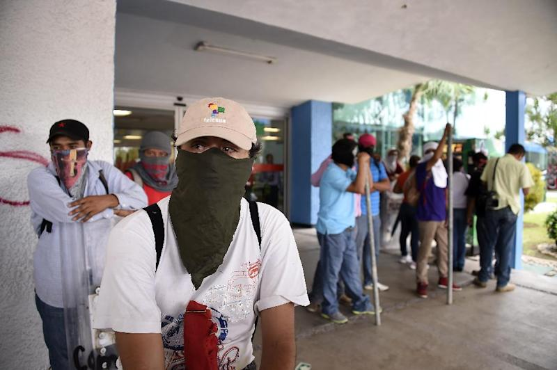 Masked demonstrators block the entrances of the airport in Acapulco, Mexico on November 10, 2014 (AFP Photo/Ronaldo Schemidt )