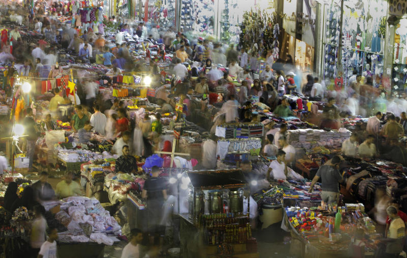 Egyptian crowd for shopping at a popular market to mark Eid el-Fitr holiday, which caps the Muslim fasting month of Ramadan, in Cairo, Egypt late Wednesday, Aug. 15, 2012. (AP Photo/Amr Nabil)