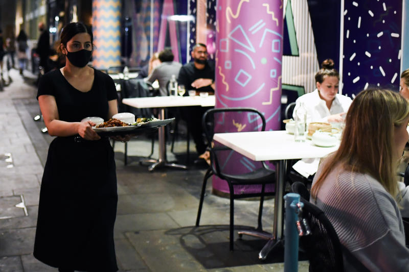 A waitress wears a protective mask as she serves customers outside a restaurant in Soho, in London, Tuesday, Sept. 22, 2020. Britain's Prime Minister, Boris Johnson, has announced that pubs and restaurants closing at 10pm, due to the spike of cases of coronavirus across the United Kingdom. (AP Photo/Alberto Pezzali)