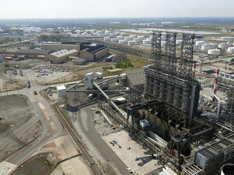 FILE - In this Sept. 21, 2017 file photo, petroleum coke, the grainy black byproduct of refining Canadian tar sands oil, is visible at the BP Whiting refinery in East Chicago, Ind. New York City officials say they will begin the process of dumping about $5 billion in pension fund investments in fossil fuel companies, including BP, because of environmental concerns. (DroneBase via AP, File)