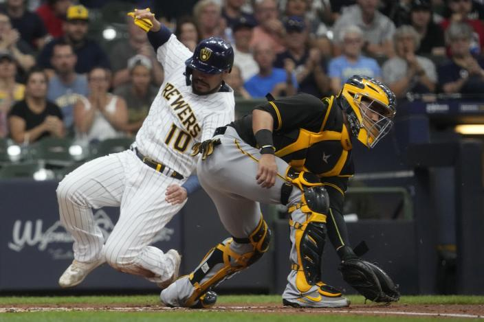 Milwaukee Brewers' Omar Narvaez slides safely past Pittsburgh Pirates catcher Michael Perez during the second inning of a baseball game Friday, June 11, 2021, in Milwaukee. Narvaez scored from second on a hit by Jackie Bradley Jr.. (AP Photo/Morry Gash)
