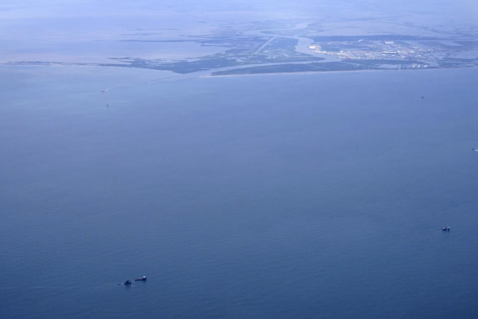 The capsized lift boat Seacor Power and two rescue boats, bottom left, are seen seven miles off the coast of Louisiana in the Gulf of Mexico Sunday, April 18, 2021. The vessel capsized during a storm on Tuesday. Port Fourchon and Bayou Lafourche, where the ship left port, are seen above. (AP Photo/Gerald Herbert)