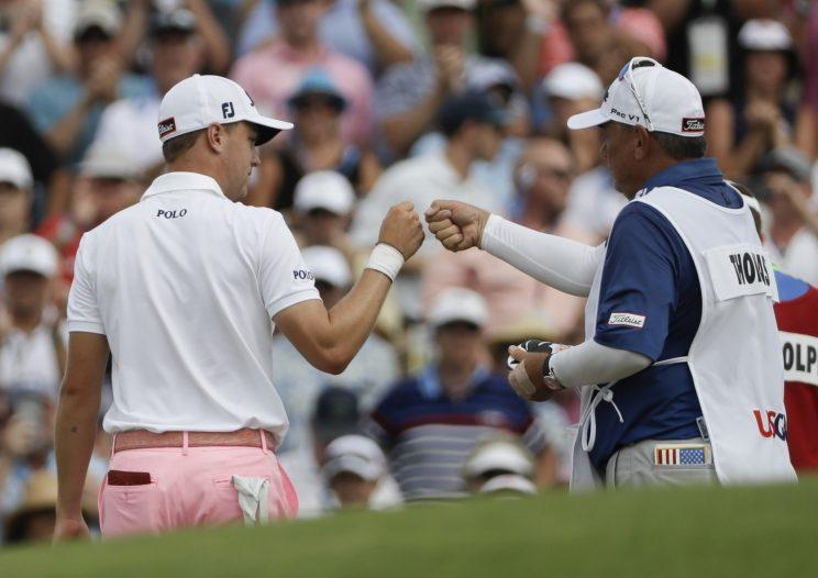 Justin Thomas is congratulated by his caddie after an eagle on 18 gave him a 9-under 63. (AP)