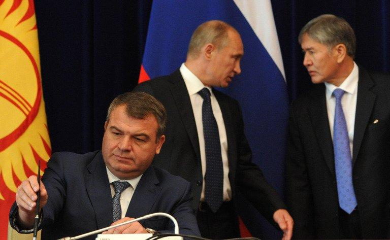 Then-Russian defence minister Anatoly Serdyukov (left) signs a document as President Vladimir Putin (centre) and his Kyrgyz counterpart Almazbek Atambayev (right) speak at Atambayev's residence near Bishkek on September 20, 2012. Russian investigators said Friday they may press charges against Serdyukov after he refused to answer questions about his alleged role in an illegal property scheme