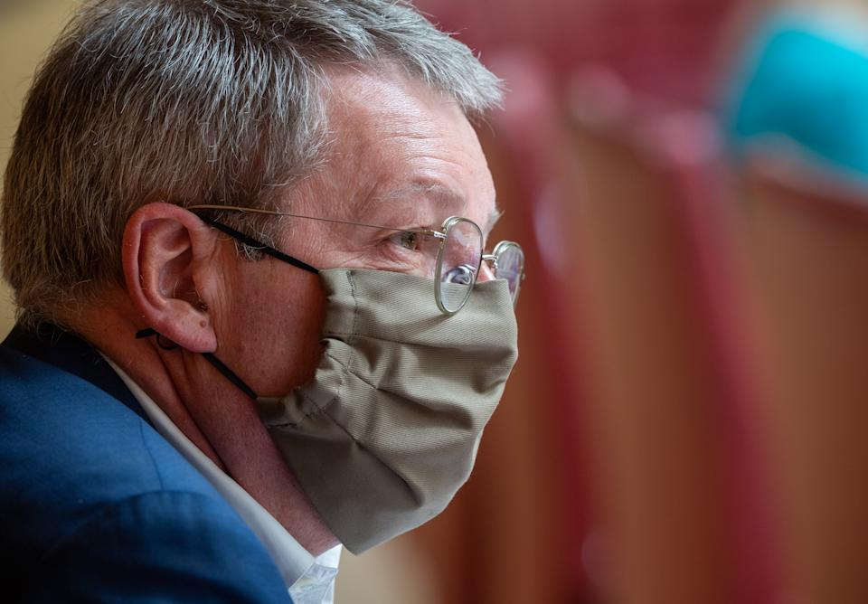 24 April 2020, Bavaria, Munich: Ernst Weidenbusch (CSU), member of the state parliament, is following the session of the Bavarian parliament with a face mask. Topics of the session include the second reading of the Corona supplementary budget and other legislative projects of the state government in the current pandemic. Photo: Peter Kneffel/dpa (Photo by Peter Kneffel/picture alliance via Getty Images)