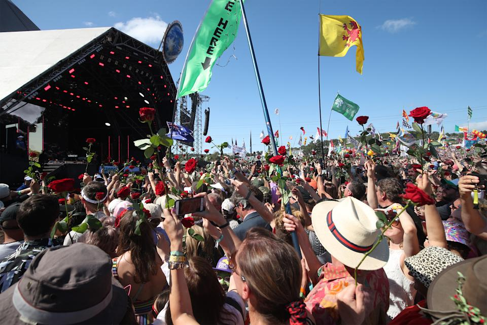 The crowd are handed out roses during a duet between Kylie Minogue with guest Nick Cave on the Pyramid Stage on the fifth day of the Glastonbury Festival at Worthy Farm in Somerset. (Photo by Yui Mok/PA Images via Getty Images)