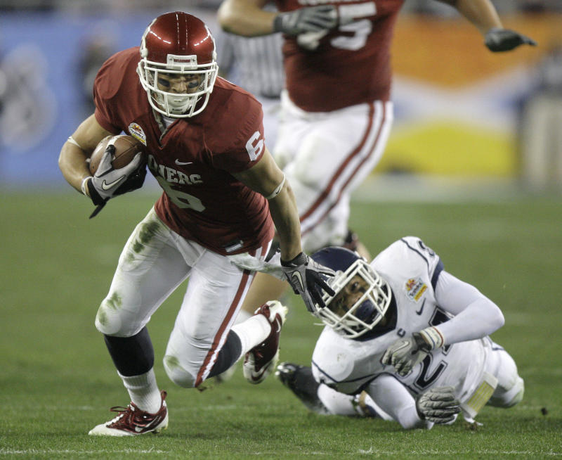 Oklahoma Sooners wide receiver Cameron Kenney (6) slips past the reach of Connecticut cornerback Dwayne Gratz (24) during the third quarter of the Fiesta Bowl NCAA college football game Saturday, Jan. 1, 2011, in Glendale, Ariz. (AP Photo/Paul Connors)