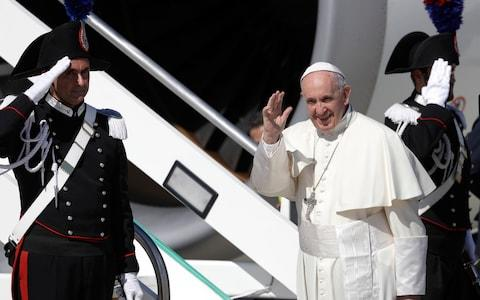 Pope Francis waves as he boards the plane for his five-day trip to Colombia, at Rome's Leonardo da Vinci international airport  - Credit: Gregorio Borgia/AP