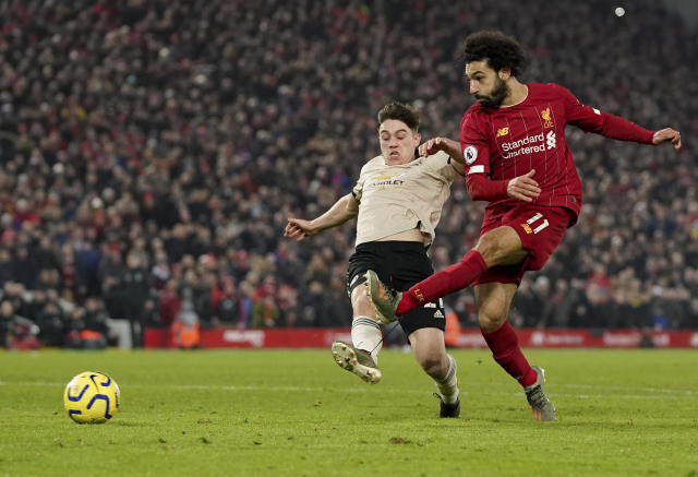 Liverpool's Mohamed Salah, right, shoots to score his side's second goal during the English Premier League soccer match between Liverpool and Manchester United at Anfield Stadium in Liverpool, Sunday, Jan. 19, 2020.(AP Photo/Jon Super)