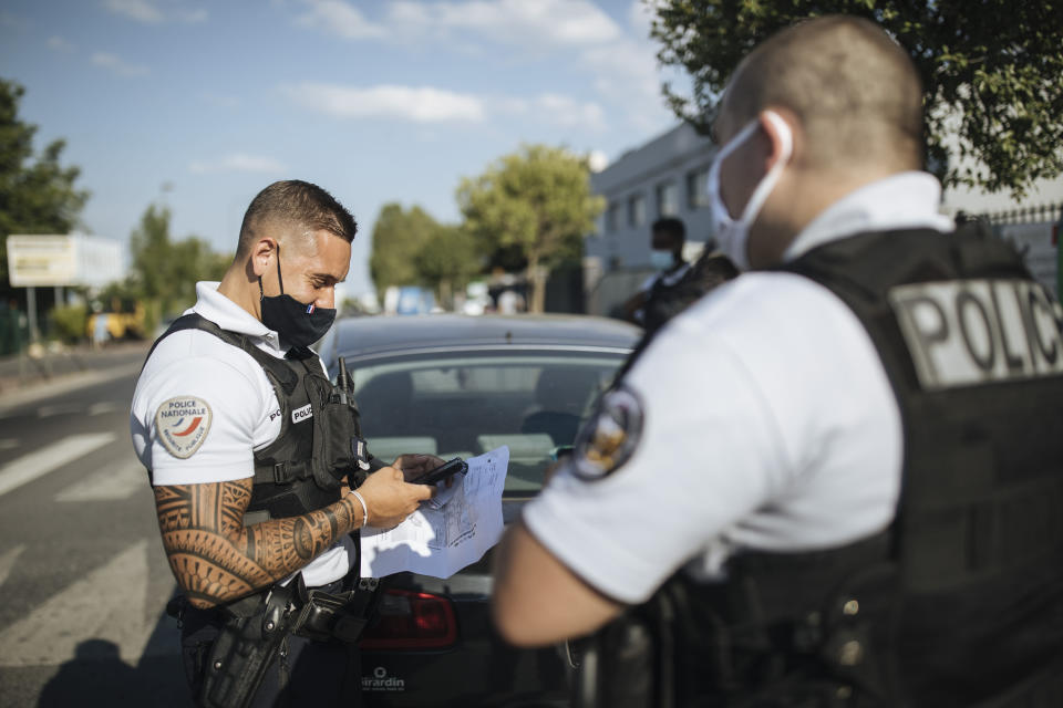 """Police officer Victor, 26, left, checks documents as he patrols in Paris suburb Garges-les-Gonesse Tuesday, June, 15, 2021. Clement, right, and Victor, with tattoed arms, refused, like many officers, to give their surnames to reporters who went out on patrol with them. They said they were concerned for their safety amid an upsurge of anti-police violence, including two murders of police officials in April and May. """"With everything going on, we don't give our names,"""" Clement said. """"It's also to protect our families."""" (AP Photo/Lewis Joly)"""