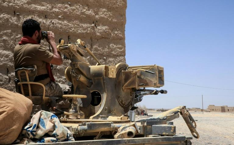 A fighter with forces loyal to Yemen's Saudi-backed government holds a position against Huthi rebels in Yemen's northeastern province of Marib