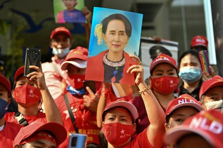 Myanmar migrants in Thailand hold portraits of Aung San Suu Kyi as they take part in a demonstration in Bangkok