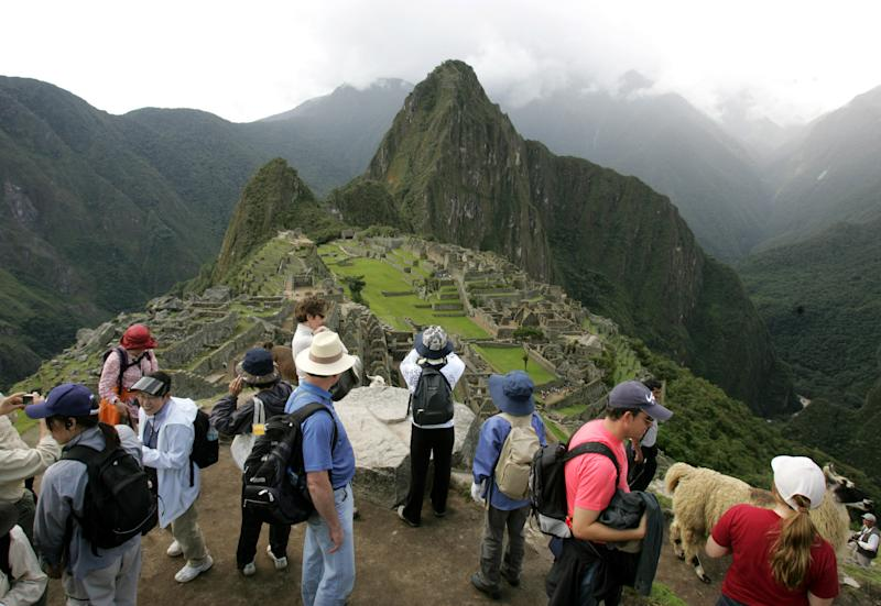 FILE - In this March 26, 2008 file photo, tourists look at the Inca citadel of Macchu Picchu in Peru. The government is looking to shift some of the tourist burden from Machu Picchu, to Choquequirao, with a plan to build the first aerial tramway that will make Choquequirao reachable in just 15 minutes from the nearest highway. (AP Photo/Martin Mejia, File)