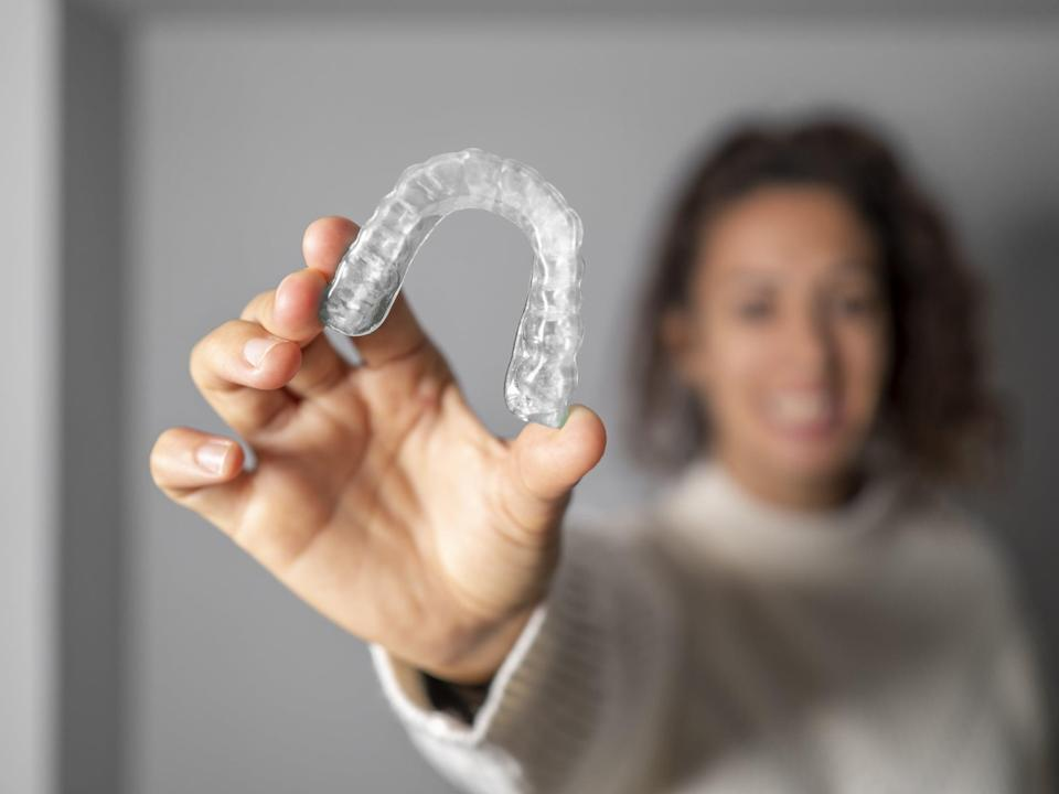 Young woman holding an invisible, transparent translucent orthodontics. Focus on orthodontics.