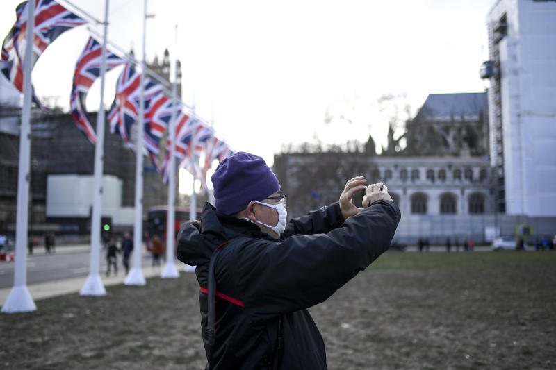 A man wearing a mask takes a picture in Parliament Square, in London, Saturday, Feb. 1, 2020. Two cases of coronavirus have been confirmed in Britain. The World Health Organization declared a global health emergency over the coronavirus outbreak. (AP Photo/Alberto Pezzali)