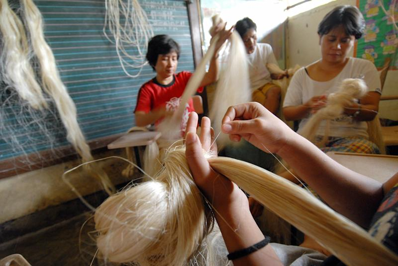 FILE PHOTO: Women from Boyuan village near the Mayon volcano continue their livelihood of weaving abaca fiber, one of the region's chief industries, at the government evacuation center, August 14, 2006, in Legaspi, the Philippines. (Photo: ROMEO GACAD/AFP via Getty Images)