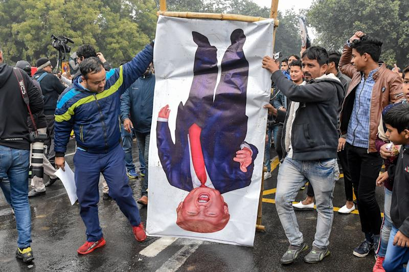 """People hold a poster representing US President Donald Trump (C) to protest against the US authorities for the killing of Iranian commander Qasem Soleimani in Iraq, during a demonstration near the US embassy in New Delhi on January 7, 2020. - A US drone strike killed top Iranian commander Qasem Soleimani at Baghdad's international airport on January 3, dramatically heightening regional tensions and prompting arch enemy Tehran to vow """"revenge"""". (Photo by Prakash SINGH / AFP) (Photo by PRAKASH SINGH/AFP via Getty Images)"""