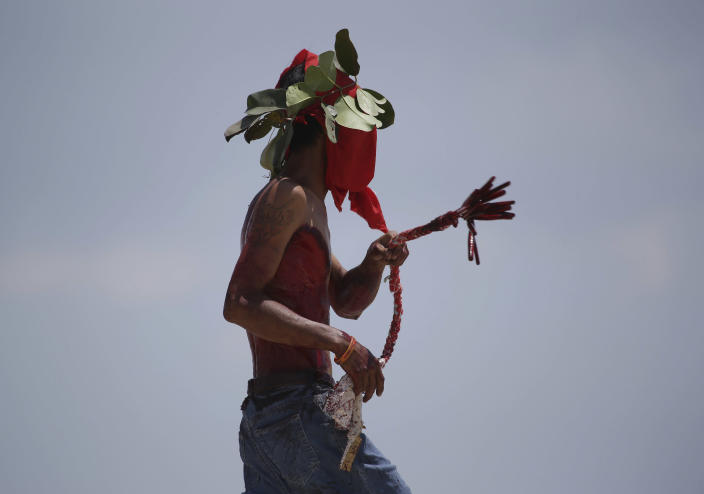 A Filipino hooded penitent flagellates himself during Good Friday rituals at Cutud, Pampanga province, northern Philippines on March 29, 2013. Several Filipino devotees had themselves nailed to crosses Friday to remember Jesus Christ's suffering and death, an annual rite rejected by church leaders in this predominantly Roman Catholic country. (AP Photo/Aaron Favila)