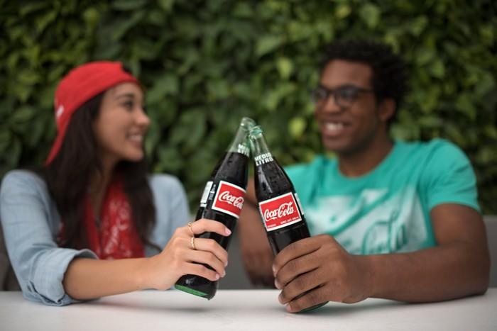 A man and woman clinking their Coca-Cola bottles together while seated and talking outside.