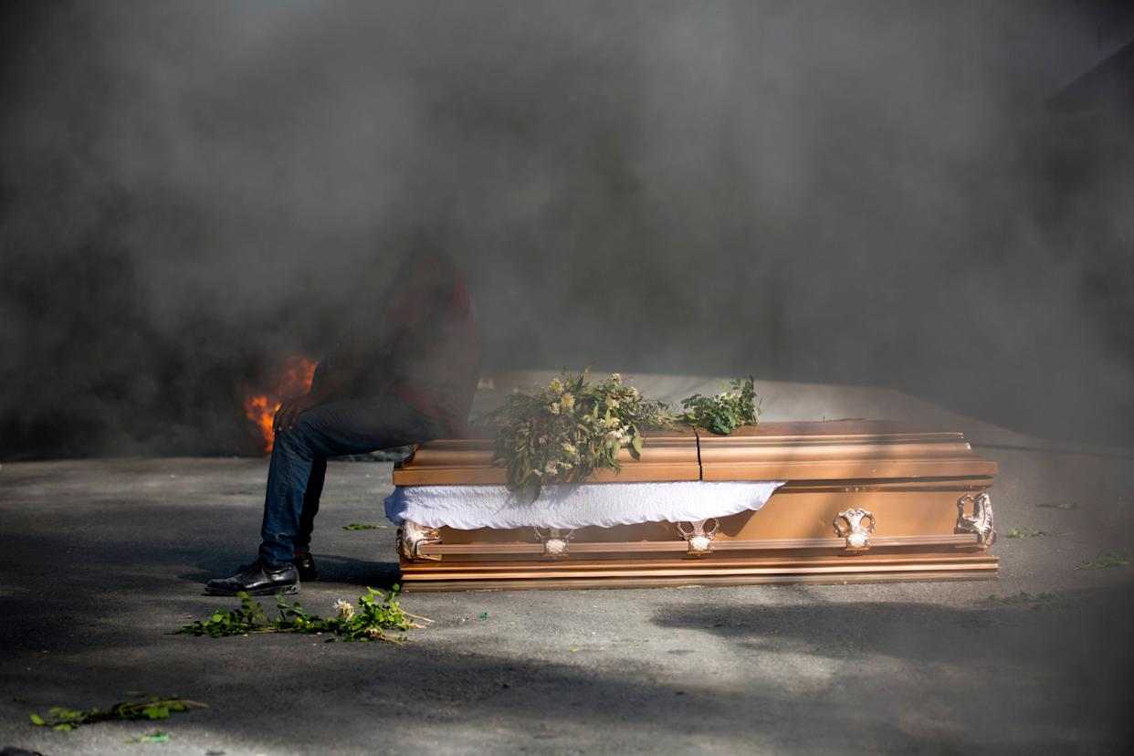 A demonstrator sits on the coffin containing the body of a protester who was killed during previous protests in Port-au-Prince, Haiti, Monday, March 4, 2019. Protesters are angry about skyrocketing inflation and the government's failure to prosecute embezzlement from a multi-billion Venezuelan program that sent discounted oil to Haiti. (AP Photo/Dieu Nalio Chery)