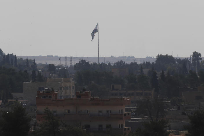 In this photo taken from the Turkish side of the border between Turkey and Syria, in Akcakale, Sanliurfa province, southeastern Turkey, Syria's opposition flag flies on a pole in Tal Abyad, Syria, Wednesday, Oct. 23, 2019. Russian media reports say Russian military police have started patrols in northern Syria as a Turkish-Russian agreement giving Syrian Kurdish fighters 150 hours to withdraw from almost the entire northeast border region of Syria came into effect. (AP Photo/Lefteris Pitarakis)