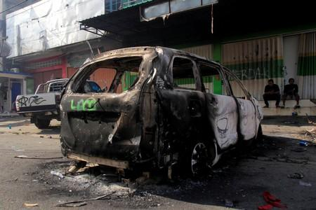 A burnt car is pictured after a riot in Jayapura, Papua