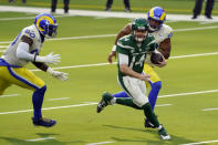New York Jets quarterback Sam Darnold (14) is chased by Los Angeles Rams' Michael Brockers, left, and Justin Hollins during the first half of an NFL football game Sunday, Dec. 20, 2020, in Inglewood, Calif. (AP Photo/Jae C. Hong)