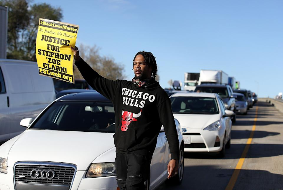 A Black Lives Matter protester holds a sign as he marches on Interstate 5.