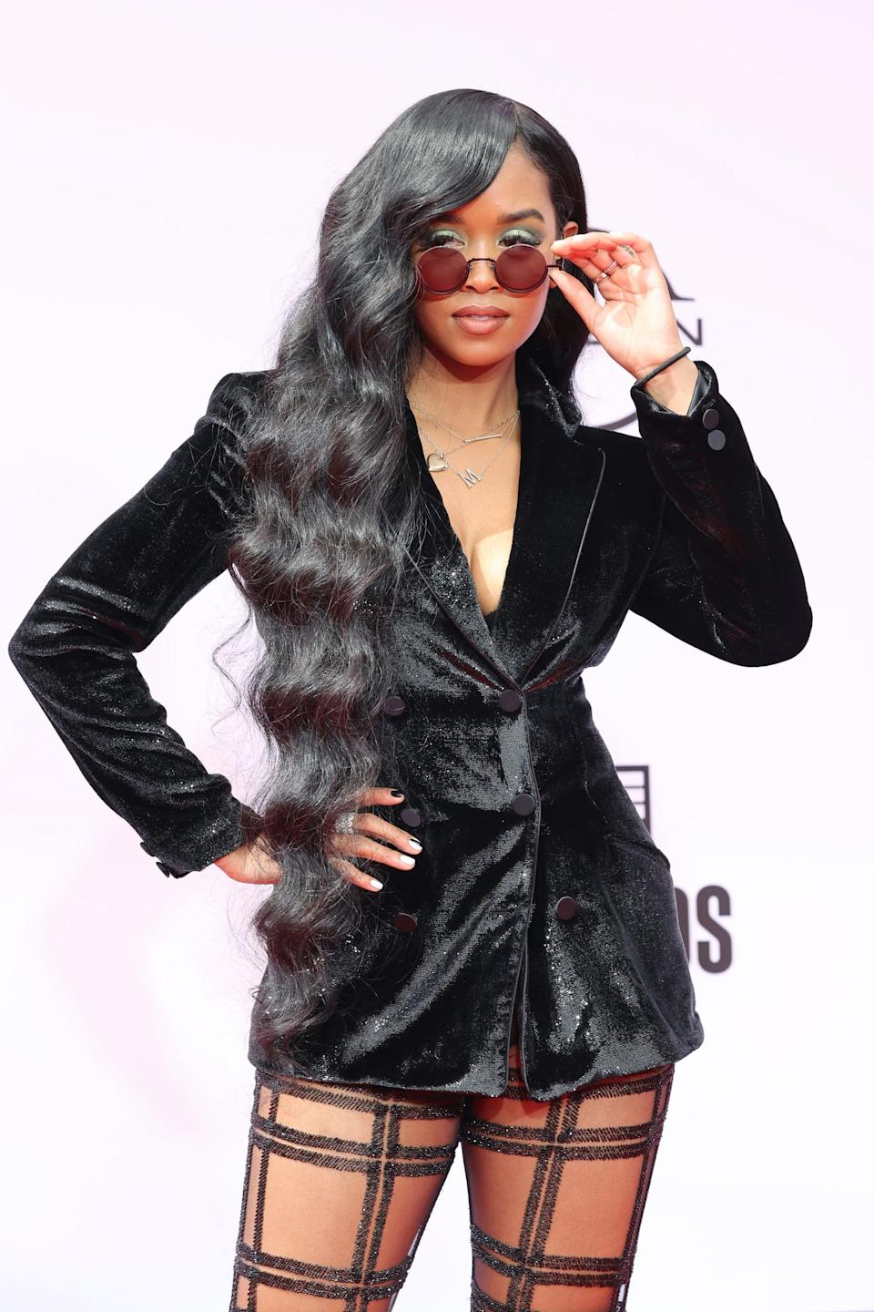 <p>H.E.R. may have gone for a vibrant green eyeshadow, but she kept her manicure subtle with a black and white design.</p>