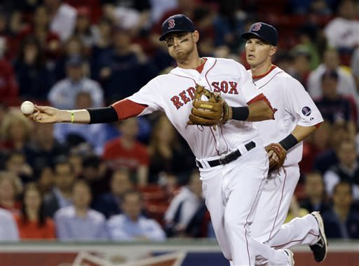 Boston Red Sox third baseman Will Middlebrooks throws to first to get Minnesota Twins' Trevor Plouffe on a grounder while shortstop Stephen Drew, right, watches during the fourth inning of a baseball game at Fenway Park in Boston, Tuesday, May 7, 2013. (AP Photo/Elise Amendola)