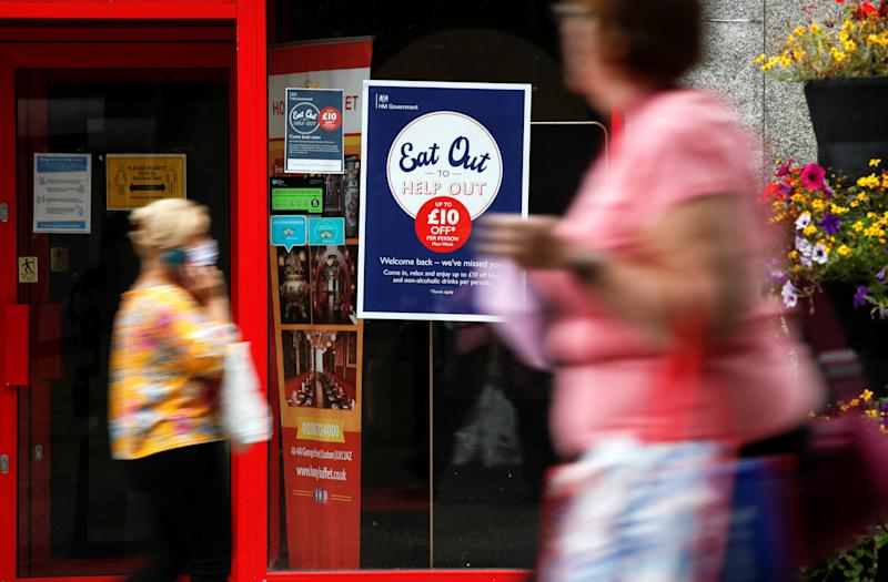 "People walk past a take-out restaurant with an ""Eat out to help out"" poster in the window, as the outbreak of the coronavirus disease (COVID-19) continues, in Luton, Britain August 6, 2020. REUTERS/Paul Childs"