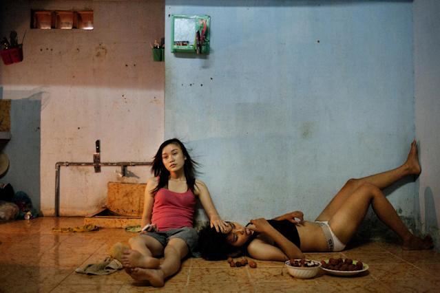 In this photo provided on Friday Feb. 15, 2013 by World Press Photo, the 1st prize Contemporary Issues Stories by Maika Elan, Vietnam, for Most, shows Phan Thi Thuy Vy and Dang Thi Bich Bay, who have been together for one year, watch television to relax after studying at school. Vietnam has historically been unwelcoming to same-sex relationships. But its communist government is considering recognizing same-sex marriage, a move that would make it the first Asian country to do so, despite past human rights issues and a long-standing stigma. In August 2012, the country's first public gay pride parade took place in Hanoi, Da Nang, Vietnam, June 22, 2012. (AP Photo/Maika Elan, Most)