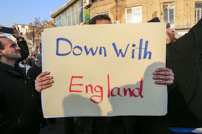 """An Iranian protester holds a """"Down with England"""" placard outside the British embassy in Tehran on Sunday (Picture: AFP/Getty)"""