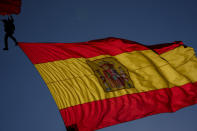 A paratrooper carries a Spanish flag during a military parade to celebrate a holiday known as 'Dia de la Hispanidad' or Hispanic Day in Madrid, Spain, Tuesday, Oct. 12, 2021. Spain commemorates Christopher Columbus' arrival in the New World and also Spain's armed forces day. (AP Photo/Manu Fernandez)