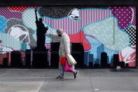 A man wears a protective face mask as he walks past closed stores in Manhattan during the outbreak of the coronavirus disease (COVID-19) in New York