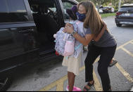 Dolphin Bay Elementary School Assistant Principal Janet Blano Soto greets students in the car line, Wednesday, Aug. 18, 2021 in Miramar, Fla. More than 261,000 Broward County Public Schools (BCPS) students headed back to school to begin the 2021/22 school year. (Joe Cavaretta/South Florida Sun-Sentinel via AP)